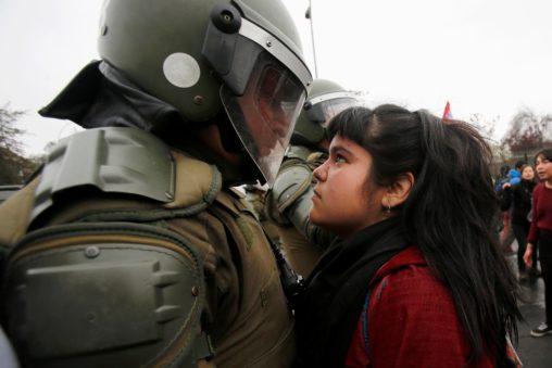 Una manifestante mira a un policia antidisturbios durante una protesta en el aniversario del golpe de estado de 1973 (Santiago, Chile 11 de septiembre de 2016) © Carlos Vera Mancilla/Reuters