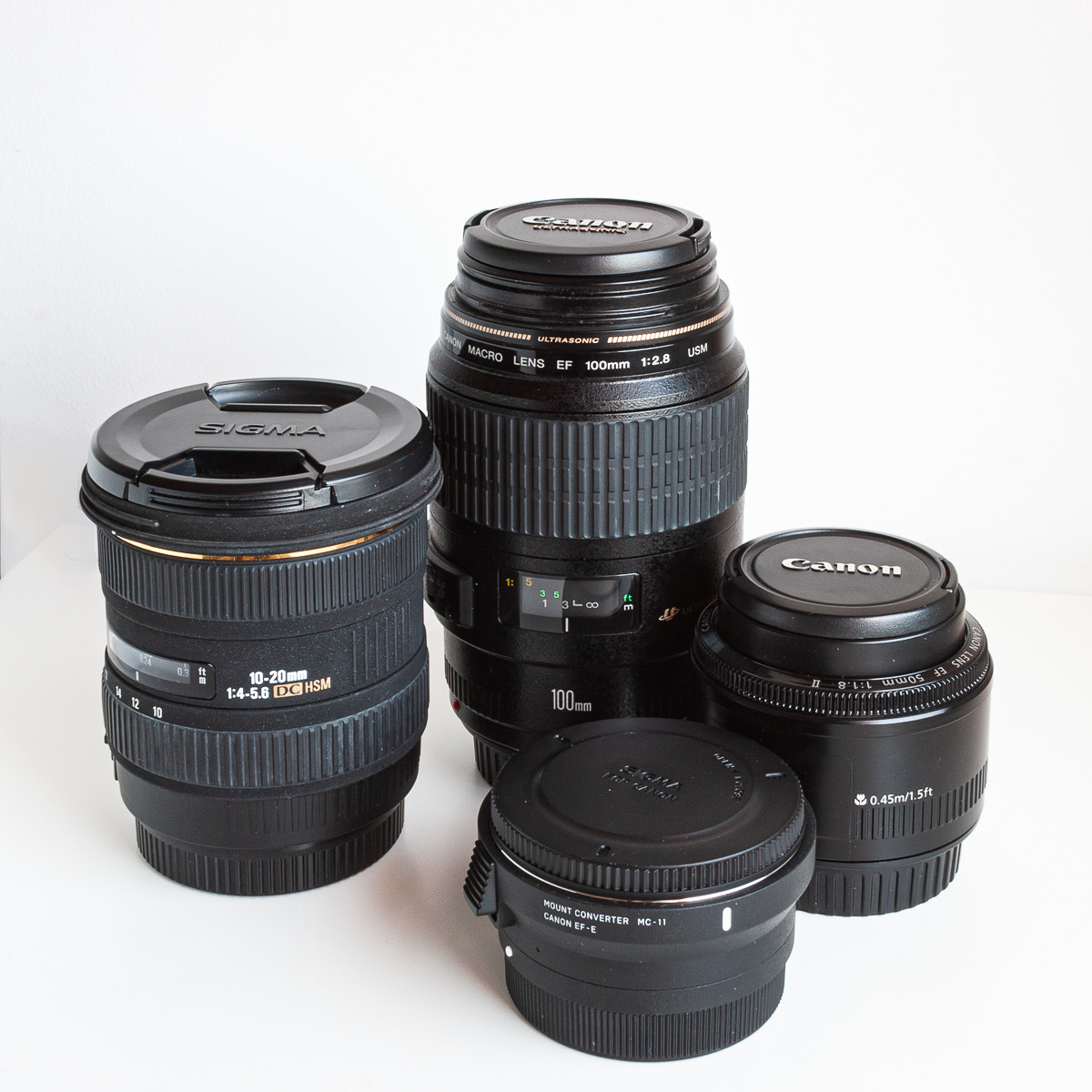 adaptador MC-11 junto al Sigma 10-20mm, el Canon 100mm Macro USM y el Canon 50mm 1.8 II